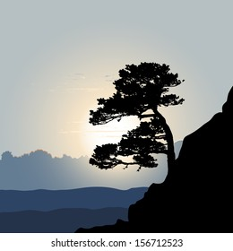 Tree silhouette on a mountain background