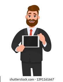 Trendy, happy young bearded business man showing/holding blank screen of digital tablet computer in hands. Modern technology, latest trends, digital gadget and device concept illustration in cartoon.
