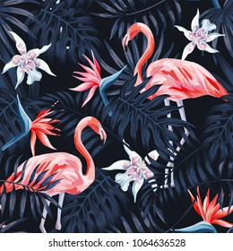 Tropical birds pink flamingo exotic flowers bird of paradise (strelitzia) dark blue palm leaves black background seamless vector pattern