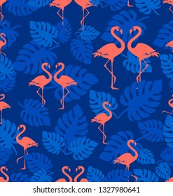 Tropical flamingo pattern. Coral flamingo. A flock of tropical birds with leaves of a tropical plant. Seamless pattern. Park of birds. Exotic birds on a dark blue background.