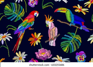 Tropical summer night. Seamless vector pattern with parrots, toucan, flowers and palm leaves on black  background. Stylized embroidered texture. Vintage motifs.