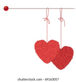 Two balls of threads in the form of heart hanging on a knitting spoke