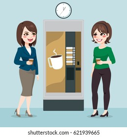 Two beautiful young business woman team having coffee from vending machine on office break time