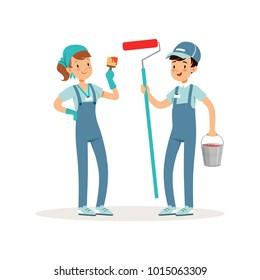 Two cheerful volunteers with paint bucket, brush and roller in hands. Social workers. Kids in blue working overalls ready to work. Cartoon pupils. Flat vector design