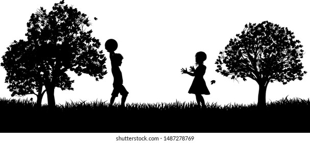 Two children, a boy and a girl, playing throw and catch in a park in silhouette