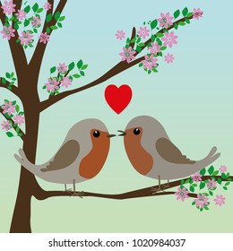 Two cute robins in love in a in a blossom tree