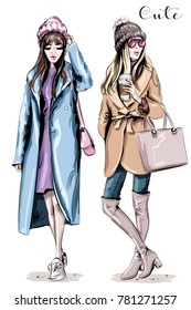 Two fashion women. Hand drawn stylish beautiful women in winter clothes. Fashion winter outfits. Sketch.
