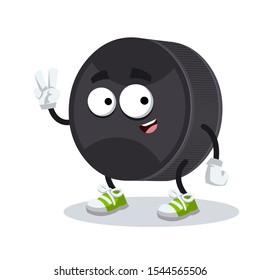 Two finger victory sign cartoon black rubber hockey puck character mascot smiling on white background