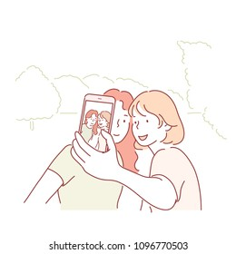 Two girls are taking pictures outdoors on their cell phones. hand drawn style vector doodle design illustrations.