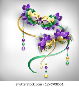 Two gold, carnival masks, decorated with purple and green feathers on gray background. Fat Tuesday. Mardi Gras.