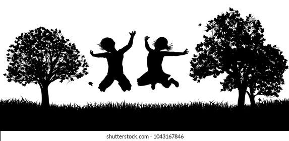 Two happy children outdoors in a field of grass jumping for joy in silhouette