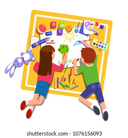 Two kids boy & girl paint & draw one picture on paper using pencils, markers & paintbrush laying with toys on carpet. Top view. Flat style character vector illustration isolated on white background