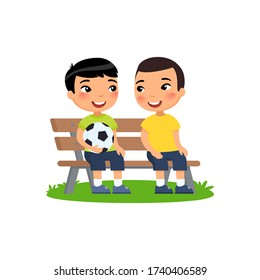Two little Asian boys with soccer ball sit on bench. Summer holidays, recreation, sports, hobbies.