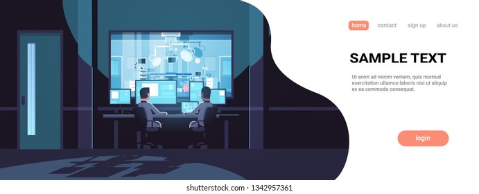 two men looking at monitors sitting behind glass window hospital operating table medical surgery room dark office interior surveillance security system flat horizontal copy space