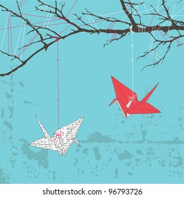 Two paper cranes hanging on tree branch