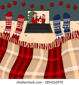 Two people are watching New year and Christmas movie on the bed under the burgundy traditional plaid on laptop in knitted red and blue socks