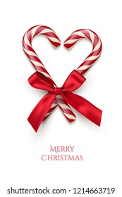 Two red striped candy cane in heart shape with red bow and Merry Christmas text isolated on white background. Vector Christmas design element