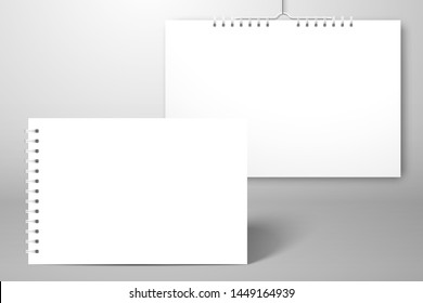 Two white blank spiral notebooks, albums or calendars. One stands on the surface, the second hangs near the wall.  Mockup for design with shadow