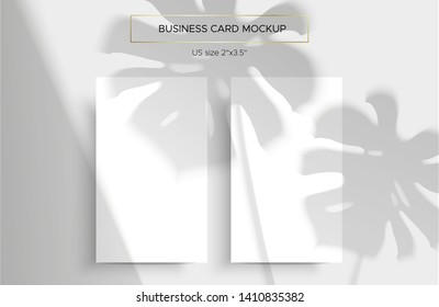Two White Business cards Mockup. Natural lighting overlays shadows on top. Scene of Tropical Leaf Shadows from the window. A monstera leaf. Photo-realistic vector illustration. Cards 2x3.5 inch.