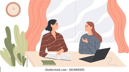 Zwei Frauen sitzen am Schreibtisch und sprechen.