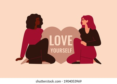 Two women sit near the big heart with the inscription