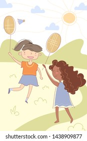 Two young multiracial children, happy little girls, playing badminton outdoors in the sunshine in a healthy active lifestyle concept