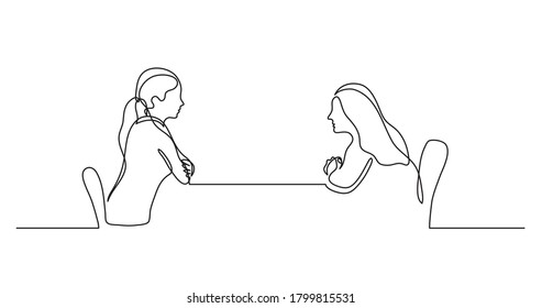 two young women sitting behind table talking