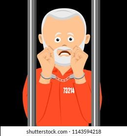 Unhappy elderly prison in handcuffs standing behind the prison bars