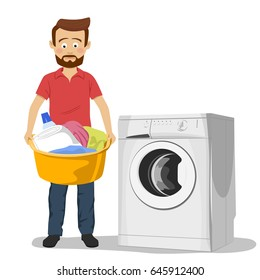 Unhappy young man standing next to washing machine with basin filled with dirty clothes