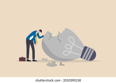 Uninspired or motivation after business failure, burnout or exhausted from crisis, no new idea or inspiration concept, depressed business man sadly standing with fail old broken lightbulb idea.