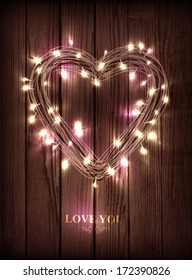 Valentine's heart-shaped wreath made of led lights on the wooden background