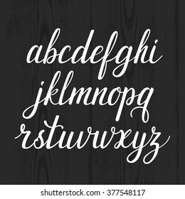Vector calligraphic alphabet. Set of beautiful hand written letters. Classic english abc. Latin characters are on the wooden background. Each letter is in one group.