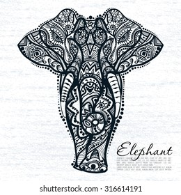 Vector drawing of a elephant with ethnic patterns of India. On the grange background. Image as a tattoo.