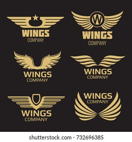 Vector golden wings logo on black backdrop. Collection of wings. Vector illustration