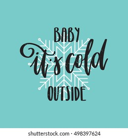 Vector hand written winter phrase - Baby it's cold outside. Black calligraphy poster isolated on blue background with white snowflake. Great print for your design