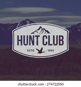 vector hunting club emblem with grunge texture on mountain landscape background