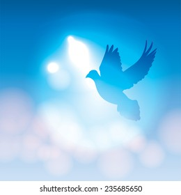 A vector illustration of a silhouetted dove flying against a blue background with soft bokeh lighting. Vector EPS 10 available. EPS file contains transparencies.