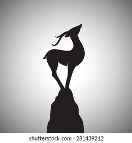Vector image of a deer standing on the rocks.