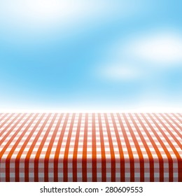 Vector picnic table covered with tablecloth on blue sky background with blurred clouds.