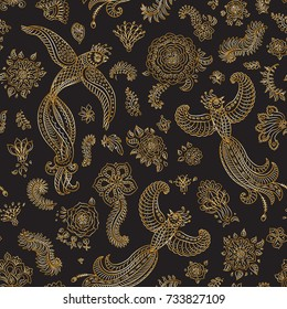 Vector seamless pattern in ethnic style.Exotic flying birds, golden contour thin line fantasy flowers with folk ornaments on black background. Embroidery, gold wallpaper, textile print, wrapping paper