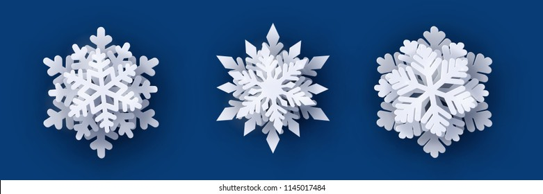 Vector set of 3 white Christmas paper cut 3d snowflakes with shadow on dark blue background. New year design elements