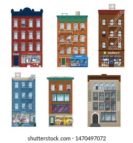 Vector set of different city buildings in Manhattan style with shops, stares, decoration elements. Shop fronts in living brick buildings. Pharmacy, gifts and antiques, laundry, cafe, book shop. Flat.