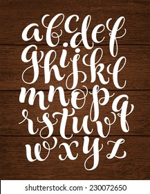 Vector set with hand written ABC letters on wood background. Calligraphy collection