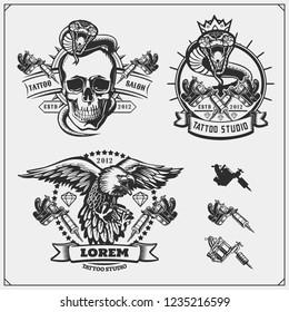 Vector set of tattoo salon labels, badges and design elements. Tattoo studio emblems with professional equipment, skull, eagle and cobra.