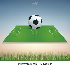 Vector soccer ball and soccer field with green grass field area and soft sky background.