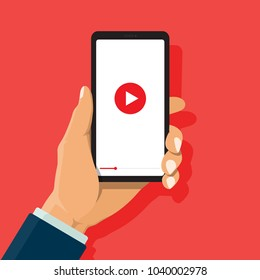 Video content marketing concept. Businessman holds smartphone with play button for reach business, online learning and training, video conference and webinar, publish information online in video.