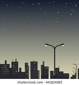 view of the city at night with street lamp in the foreground and stars in the sky