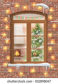View through a window on the interior of a Christmas living room with the Christmas tree and fireplace. The brick facade of the house is decorated with a garland of light bulbs. It's snowing outside.