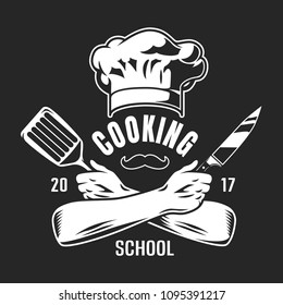 Vintage cooking classes logo with chef hat mustache crossed arms holding knife and spatula on dark background isolated vector illustration