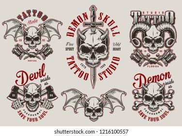 Vintage demon tattoo studio prints set with horned devil skulls crossed axes bones tattoo machines sword isolated vector illustration